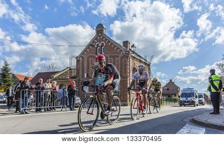 Louvil France - April 102016: Group of three cyclists riding in front of Louvil Town Hall in France during Paris Roubaix on 10 April 2016.