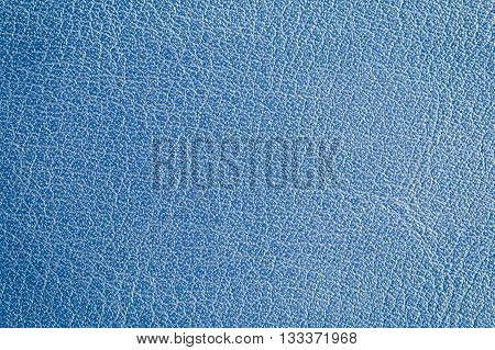 Background of close focus on blue skin of artificial waxed leather with striped made from synthetic plastic. Color tone grading from dark on the left to brighter on the right.