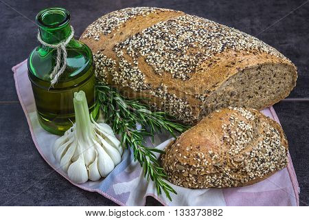Whole wheat bread and rye sprinkled with sunflower seeds poppy seeds sesame seeds next to a bottle of olive oil rosemary and garlic