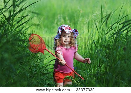 Girl in red shorts with a butterfly net catching butterflies