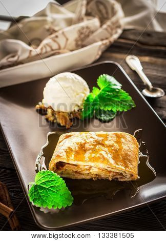 Apple strudel with ice-cream decorated by mint on ceramic plate. Selective focus.