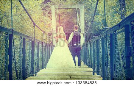 Vintage photo of happy bride and groom on a wooden bridge in the park at the wedding walk