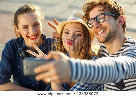 Friendship leisure summer technology and people concept - smiling friends making selfie outdoors