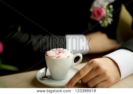 Groom's hands holding cup of coffee men