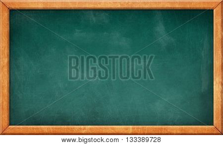 Old green dirty scratched blank blackboard in wooden frame
