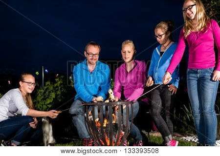 Nightly bbq party of family in their garden, they are grilling sausages on sticks in open fire