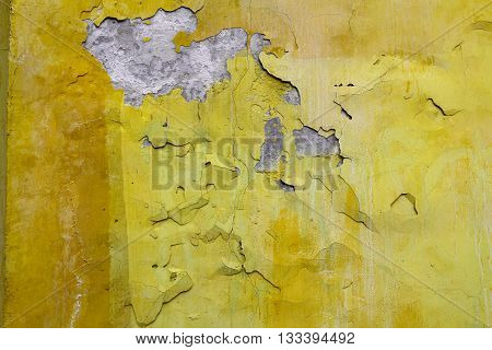 Old yellow paint with cracks on the wall