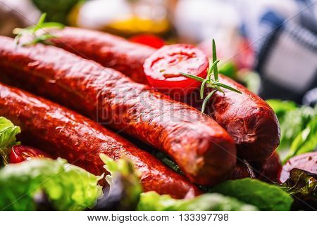 Sausage. Chorizo sausage. Raw smoked sausage with vegetable decoration.Lettuce salad herb rosemary tomato garlic olive oil.