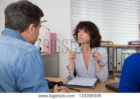 Woman Pointing On Couple While Talking At Desk In Office