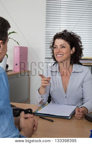Businesswoman Pointing On Man While Talking At Desk In Office
