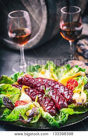 Sausage. Roasted chorizo sausage. Roasted spicy sausage chorizo home hotel or restaurant with beer vine brandy cognac whiskey.Vegetable decoration lettuce salad tomato garlic. Toned photo.