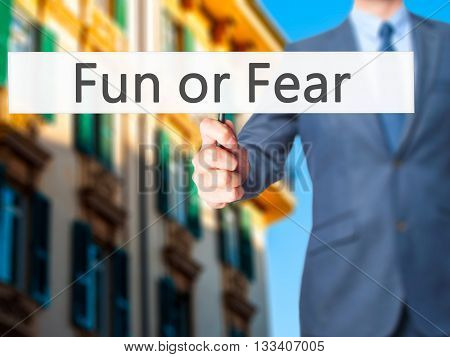 Fun Or Fear - Businessman Hand Holding Sign