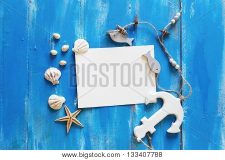 Blank paper card and seashells on wooden background
