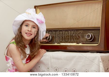 Dressy little girl turns the volume knob in an old radio. Retro style