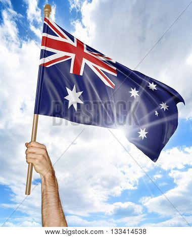 Person's hand holding the Australian national flag and waving it in the sky, 3D rendering