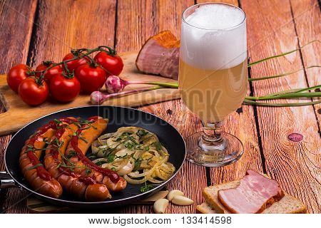 Tall elegant glass with unfiltered white beer with fried sausages tomatoes chery bread garlic and pork meat on the old wooden table