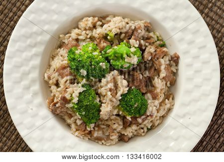 Slow cooked dish with chicken tights rice and broccoli. Close up high angle view