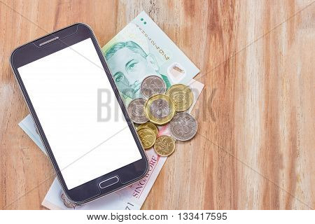 Smart phone and singapore dollar on wooden table background