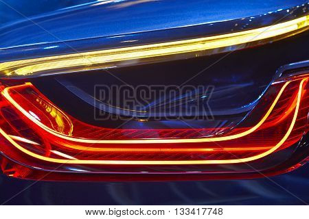 Rear car light detail in blue red tone. Vehicle part. Horizontal