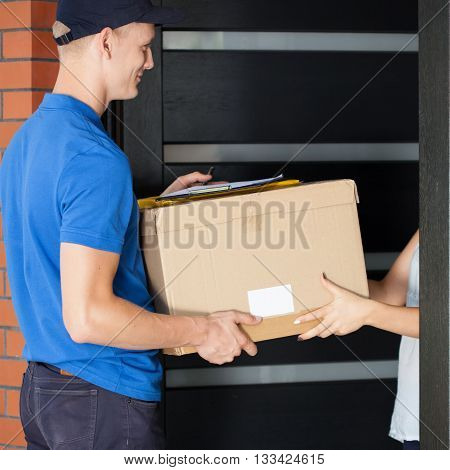 Delivery Man Giving Parcel To Homeowner