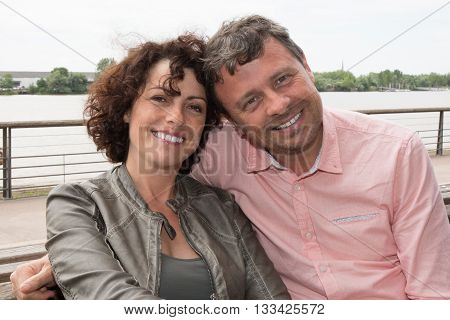 A Cheerful middle-aged couple embracing outside under cloudy sky