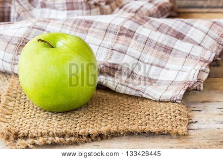Green apple with leaves on burlap on old wooden table background. green apple for healthy eating and healhcare concept for design
