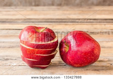 Close up of a sliced red apple on a wooden table. Fresh red apple on old wooden table background. Red apple on wood table