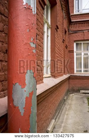 downspout with peeling off paint on the old brick building