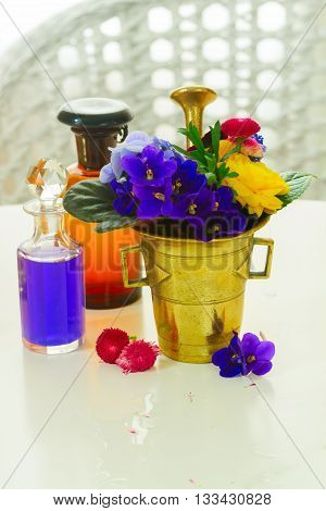 Flowers, mortar and glass bottles of potions, herbal medicine
