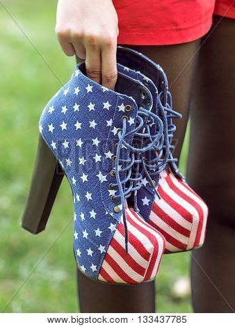 Girl holds Boots in American Flag Style
