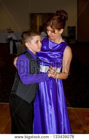 A mother who is a bridesmaid at a wedding dances with her young son at the reception.
