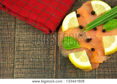 Slices of smoked salmon with lemon and chives on a wooden background. Horizontal flat top view.