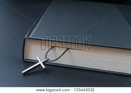 Theology Concept. Metallic Cross And Holy Bible On Black Backgro