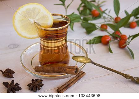 Cup of tea with spices and lemon and a sprig of nightshade flower
