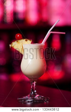 Pina Colada cocktail shot on a bar counter in a nightclub in red light
