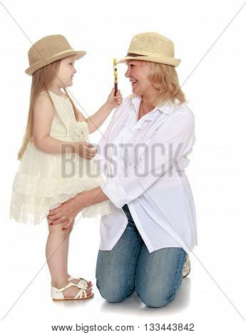 Adorable little granddaughter dressed in a white dress and a hat , consider a magnifying glass my grandmother's face - Isolated on white background