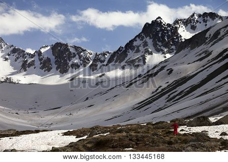 Hiker In Spring Snowy Mountains