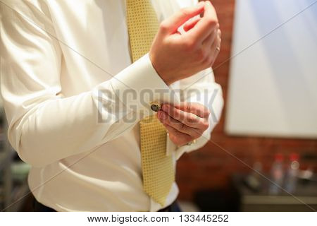 close up of a hand man how wears white shirt and cufflink. yellow tie