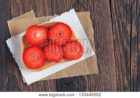 Slice of toasted bread with fresh strawberries on wooden table top view