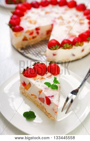Cake with strawberries gelly yogurt and cherries. Shot from above. Isolated on white background. One piece in a white plate. Vertical shot