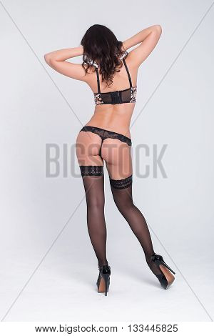 Sexy woman in a black lingerie on the white background