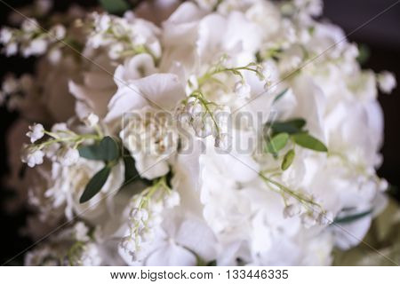 wedding bouquet of white small flowers lily-of-the-valley at girl's hand.