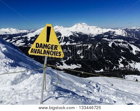 Avalanche danger sign in a mountain winter landscape