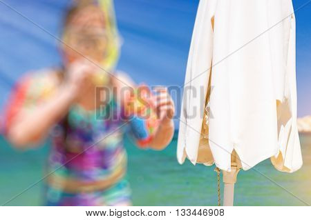Abstract blurred background with bokeh. Solar umbrella. Girl child relaxing on the shores of Cretan sea in swimming glasses with breathing tube and in rescue arm cover. Sunny sandy Livadi beach in sea Bay of resort village Bali Rethymno Crete Greece