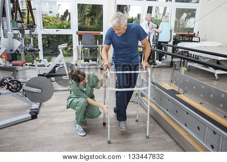 Female Nurse Assisting Senior Man With Walker In Fitness Studio