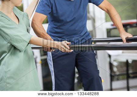 Physiotherapist Standing By Senior Man Walking Between Parallel