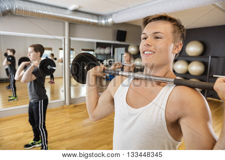 Man Lifting Barbell With Friends In Fitness Studio
