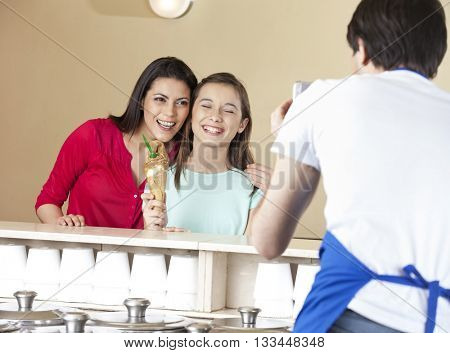 Waiter Photographing Happy Mother And Daughter With Ice Cream