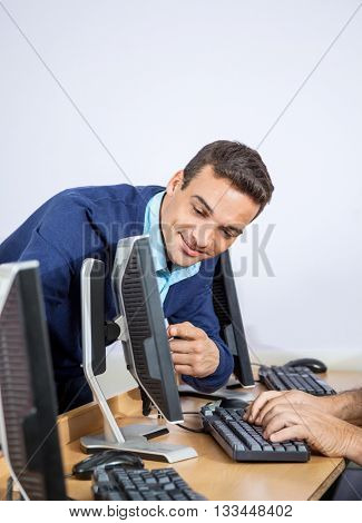 Teacher Showing Something To Senior Man On Computer In Classroom