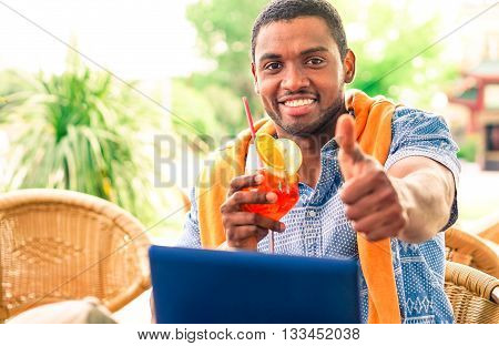Cheerful afro american man thumb up sitting at restaurant - Black guy holding cocktail glass showing okay hand sign in beach bar cafe - Concept of relaxing travel holiday and successful lifestyle